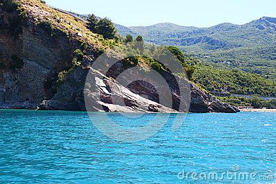 The turquoise sea meets forested rocks of the mountain in Montenegro, Europe. The inclined terrain looks wonderful.