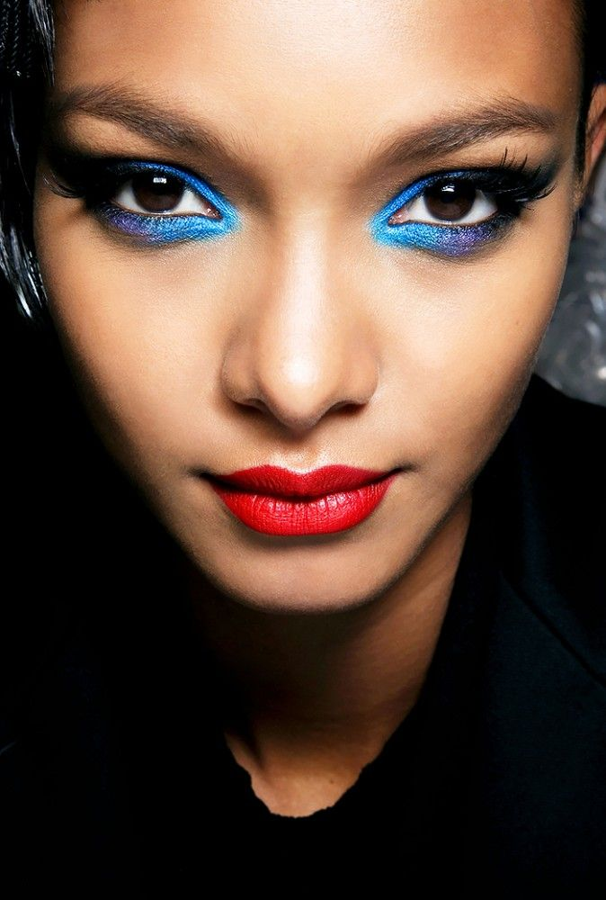 Bright blue eye shadow and a pop of red lipstick creates a attention-grabbing NYE makeup look