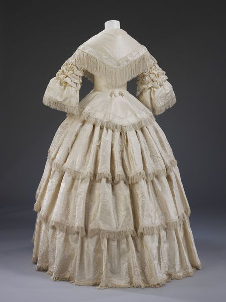 1857, England - Wedding dress - Figured silk trimmed with silk fringe, buckram stiffening