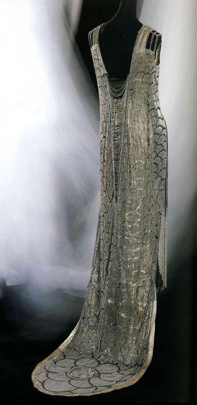 Вечернее платье. Беер, около 1919. Черная сетка с серебряным бисером и «рейнскими камнями» (искусственными драгоценностями), вышивка традиционными японскими узорами, бахрома из серебристого бисера, широкий шарф-пояс в золотистую и зеленую полоску, нижнее платье из серебристой ткани ламе.