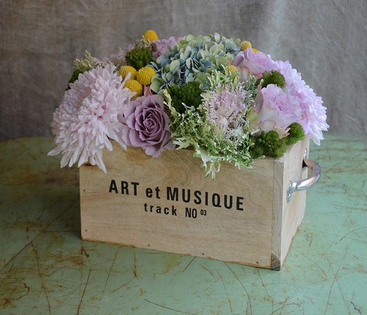 Caja de madera rústica y arreglo de flores de temporada.