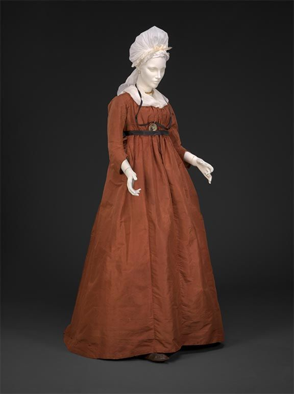 "Taffeta ""Round Gown"", About 1795-1800  The round gown"" style is updated further with a raised waist and gathered bodice which ties at center front. Vestiges of an older style of fitted bodice are visible on the inside. Internal stitching reveals the waistline was raised about three inches. A stiff taffeta material like this still suits the dress, but lighter, softer fabrics will be needed for the slim, clinging styles on the horizon."