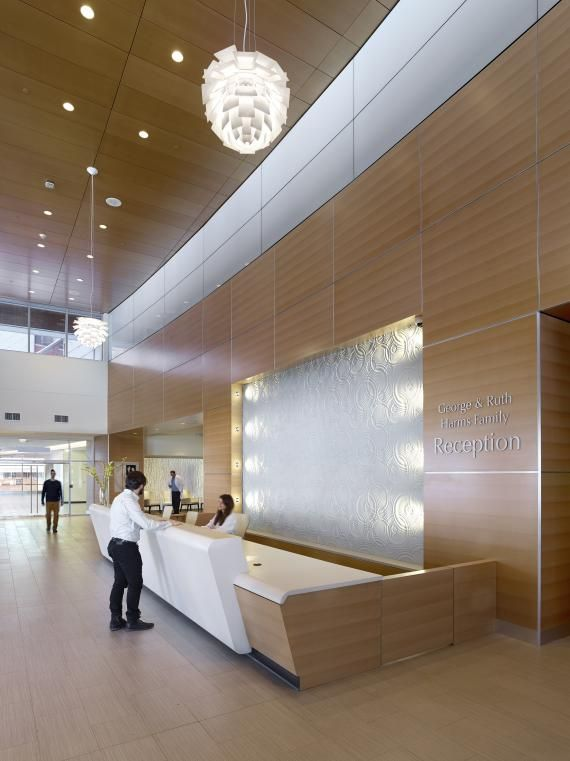 PHOTO TOUR: Ocean Medical Center Emergency Care Center in Brick, New Jersey | Healthcare Design --- In the main lobby behind the reception desk, a modular art panel with a water-like pattern adds to the sense of calmness in the space. Wood grain runs horizontally on the paneled walls. Photo: (c) Jeffrey Totaro, 2014.