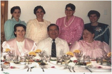 """FLDS: It's Merril """"Oink"""" Jessop again, with his first six wives. Standing at the left (blue) is Carolyn (fourth wife, escaped), seated in pink is Barbara (abusive third wife); standing in peach is Ruth (mentally-ill second wife; Barbara's sister), in lurid pink is Cathleen (sixth wife, looked terribly ill on Anderson Cooper); in pink on Merril's right is Faunita (abandoned by the family when dangerously ill with diabetes); and in green, on the right, Tammy (Ruth and Barbara's cousin)"""
