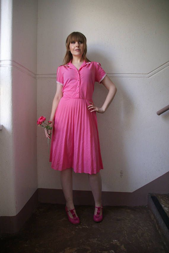 A pretty Vintage 60s 70s Secretary Dress by Smarty. In a light polyester material this mid-length dress is pink with white lace detailing on the Peter Pan Collar and capped sleeves. Has a pleated skirt and pale pink pearl buttons on the bodice with a ribbon tie back. Lovely Summer