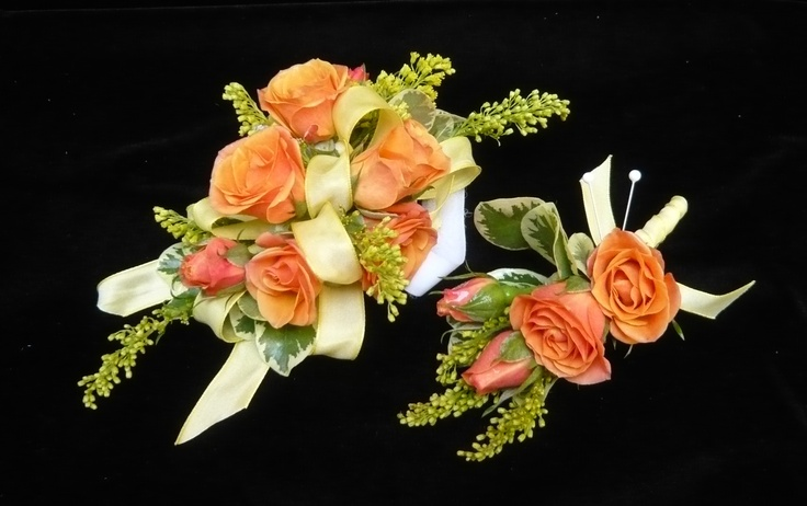 Orange roses with solidago in yellow ribbons on a velcro wristlet for a girl with a tiny wrist. #prom #corsage by Emil J Nagengast Florist in Albany, NY