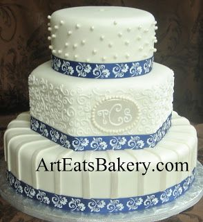 Three tier white fondant round and hexagon wedding cake with sugar pearls, monogram, curlicues, pearl stripes, and blue ribbons
