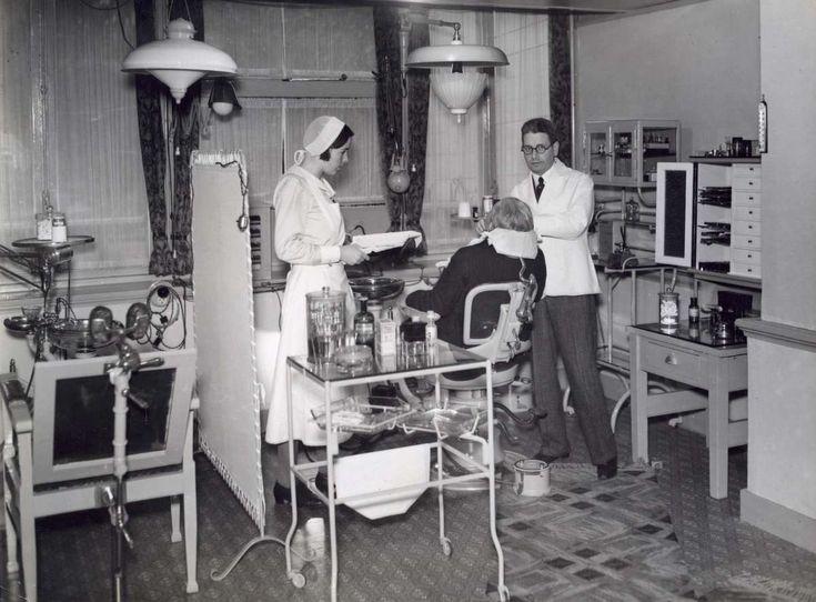 De praktijkruimte van de tandheelkundige polikliniek Cats, Amsterdam 1924. De tandarts en zijn assistente bij een patiënt in de behandelstoel.