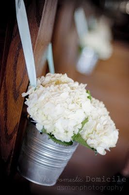 """I purchased 14 tin buckets from Target's dollar section and some pale aqua ribbon from Michaels. I ordered 2 orders of hydrangea's from Sam's Club bulk floral department at around $50.00 a pop and grabbed some floral foam from Michaels to make it a day for the """"Pew Bucket Project""""."""