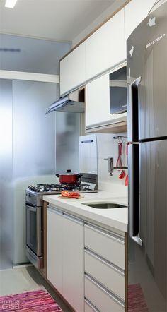 Cozinha corredor com porta de vidro de correr separando a lavanderia da cozinha. Projeto Marina Carvalho