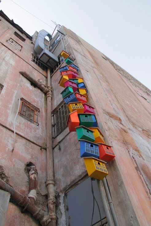 Street artist Dambo's Happy City Birds project upcycles materials and trash into birdhouses. The birdhouses themselves become art that humans can enjoy and beautify a building.
