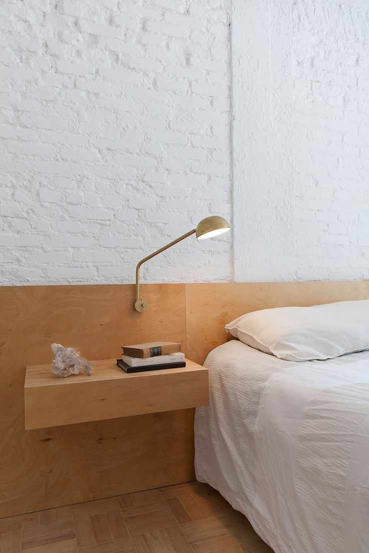 Bedroom with white painted brick wall behind the plywood bed headboard and nightstand.