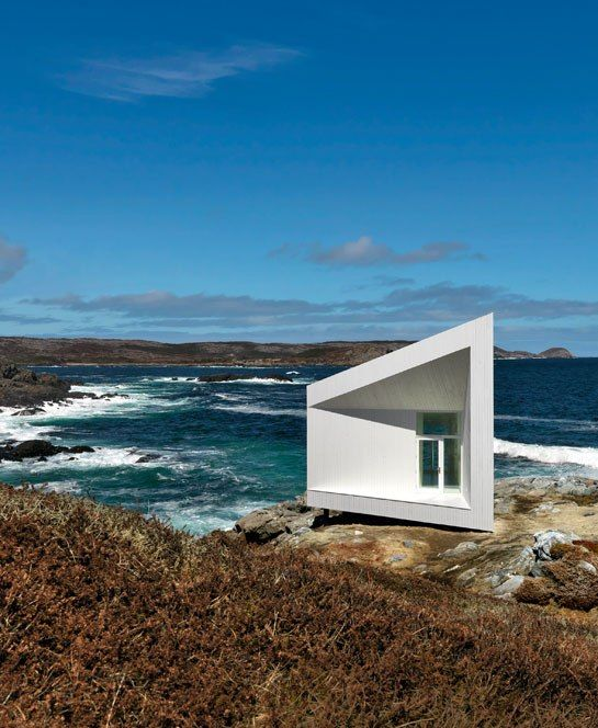 A Minimalist Artist's Cottage off the coast of fogo Island, Newfoundland. Clad in painted spruce, the compact structure is one of six studios designed by Norway-based architect Todd Saunders for the isle's artist-residency program..