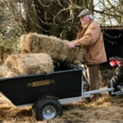 Man loading bales on to an ATV/Quad bike trailer. For more info: http://www.fresh-group.com/trailers-trolleys-and-carts.html