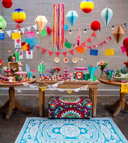 Festa de criança com tema mexicano. O espaço foi enfeitado com bandeirinhas, balões, varal de luzes e os famosos papeis picados mexicanos. Em vez de uma, eram três mesas de doces. Na frente delas, foi colocado um pufe colorido e um tapete azul estampado.
