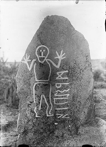 """Rune stone, Krogsta, Uppland, Sweden, from the 6th century AD, with a human figure and an inscription. One of three known rune stones in Uppland carved with the elder rune alphabet, and the only one still in its original position. The inscription is only partly deciphered - the text on the backside probably renders the word """"stone"""".  Photo taken ca. 1900"""