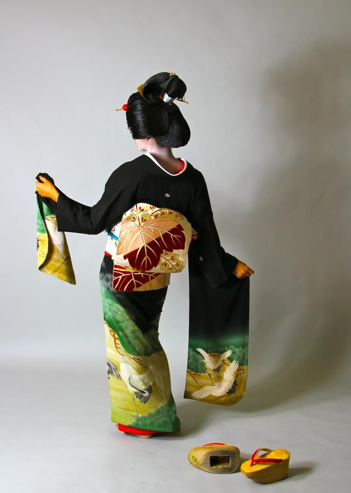 While I love the furisode, her wig/hair style is that of a geiko/geisha, where as her kimono and shoes suggest a maiko.