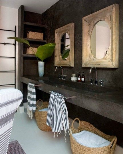 Zen bathroom with rustic wood mirrors on black stone walls over black stone floating vanity with trough sink accented with modern gooseneck faucets.