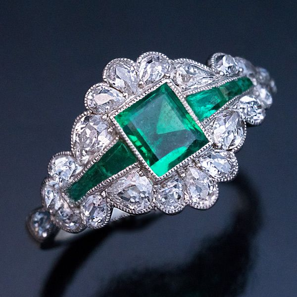 1920s A platinum milgrain engagement ring is centered with a rectangular step cut natural emerald (5 x 4.4 x 2.95 mm, approximately 0.45 ct) flanked by cha