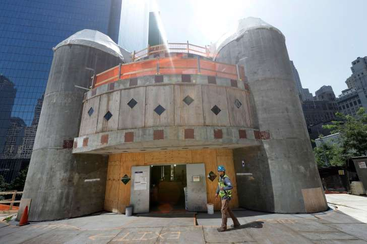 FILE- In this Aug. 10, 2017 file photo, a construction worker walks in front of the St. Nicholas National Shrine in New York. Work on the Greek Orthodox church destroyed in the Sept. 11 attacks next to the World Trade Center memorial plaza has been temporarily suspended by the construction company. It comes amid financial difficulties and questions over how funds have been managed. (AP Photo/Mark Lennihan, File)