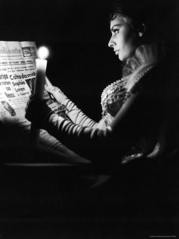 """ACTRESS SOPHIA LOREN READING NEWSPAPER BY CANDLELIGHT WHILE IN COSTUME FOR """"MADAME SANS GENE"""""""