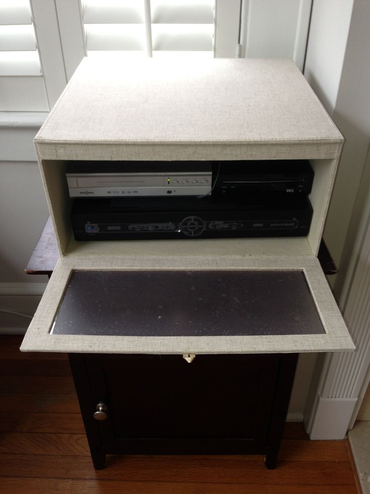 Linen sweater box from Container Store hides cable box, dvd player and wii. Front drops down for easy access while hiding the ugly appliances.  I added frosted glass film from Home Depot.