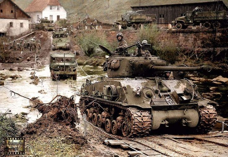 """An M4A3 (76mm) W HVSS of Combat Command """"B"""" 11th Armored Division crosses the Muhl river near Neufelden in Austria. May 3/4th 1945. A Dodge weapons carrier follows it and behind that an M4A3E2 Sherman Jumbo. (Notes :- horizontal-volute suspension..."""