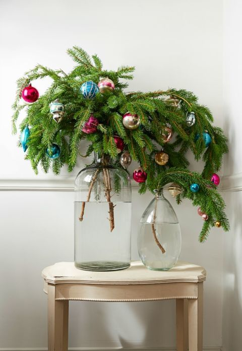 If you really don't have room for a tree, opt for this aesthetically pleasing pine arrangement instead. Simply fill oversized jars with water and insert boughs of pine or cypress. Oh, and adorn with festive ornaments, of course. Click through for more small Christmas trees and how to perfectly style them.