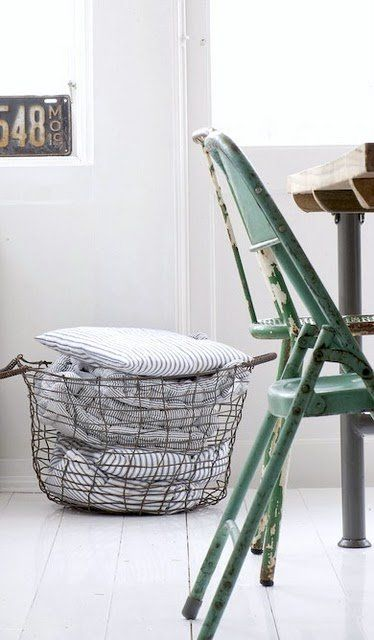 Vintage Basket good for holding laundry or blankets | Vintage Metal Chair | White Walls and lots of natural light