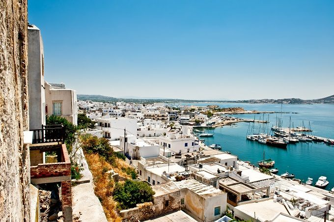 Naxos, Greece, white-washed buildings surrounding boats in the harbour.