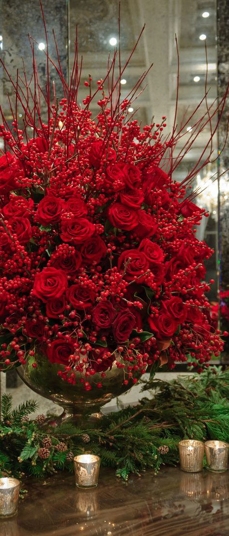 This Christmas centerpieces make use of gorgeous red roses and berries. Simple, elegant and works best surrounded by greenery and gold candles.
