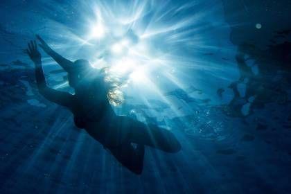 Ein Frau schwimmt bei strahlendem Sonnenschein im Freibad