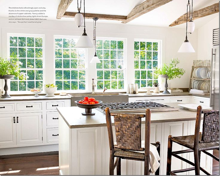 In Country Living magazine, the kitchen was shown in a close up. The pulley lights, which came from Europe are beautiful. In most kitchens, she replaces overhead cabinets with windows over the usual apron sink. The countertops are Fireslate