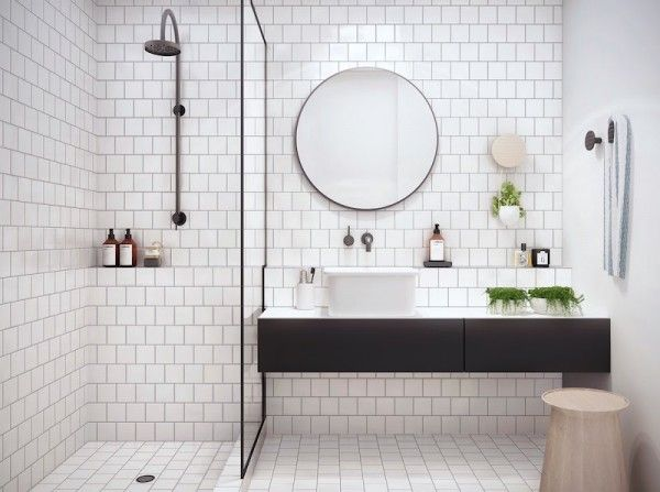Classic white #bathroom tile with round #mirror and black vanity