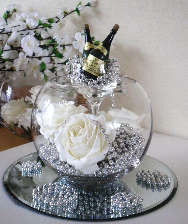 Celebration Centrepiece. Silver beads and large silk roses in a bubble bowl on a mirror plate.  A glass full of silver beads and champagne bubbles stands in the bubble bowl. www.angelfloraldesigns.co.uk