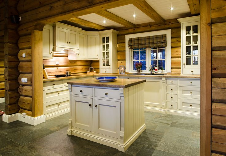 Hand painted light beige kitchen in solid pine from Os Trekultur. Worktop in stained and varnished oak. Integrated appliances and good storage solutions. The kitchen is tailored to the log cabin. The kitchen island contributes to social cooking.