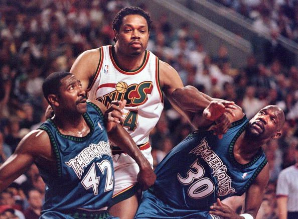 Seattle SuperSonics' Sam Perkins muscles for position against Minnesota Timberwolves Sam Mitchell and Terry Porter during first half action of their...