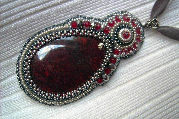 Ny-555. Sötét bordó színű Jáspis medál, ezüst és piros színű gyöngyökkel. A hímzett medál, egy szürke színű bársony szalagon van. Hossza: 56 cm. A medál mérete: 97 x 47 mm. Ára: 2200.-Ft.