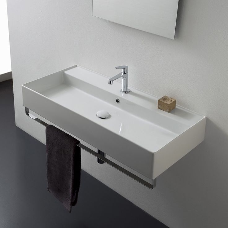 Wall mounted white ceramic bathroom sink with polished chrome towel bar. Towel bar is made of high-quality brass in a polished chrome finish. Bathroom sink has faucet hole options of one hole, no hole, or three hole and includes an overflow. Made in Italy by Scarabeo.