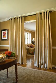 Curtains add glamour, increase privacy, buffer noise, and block drafts. Here, the entrance from the dining area to the den is framed with thick, textured panels hung from a simple rod mounted near the ceiling.