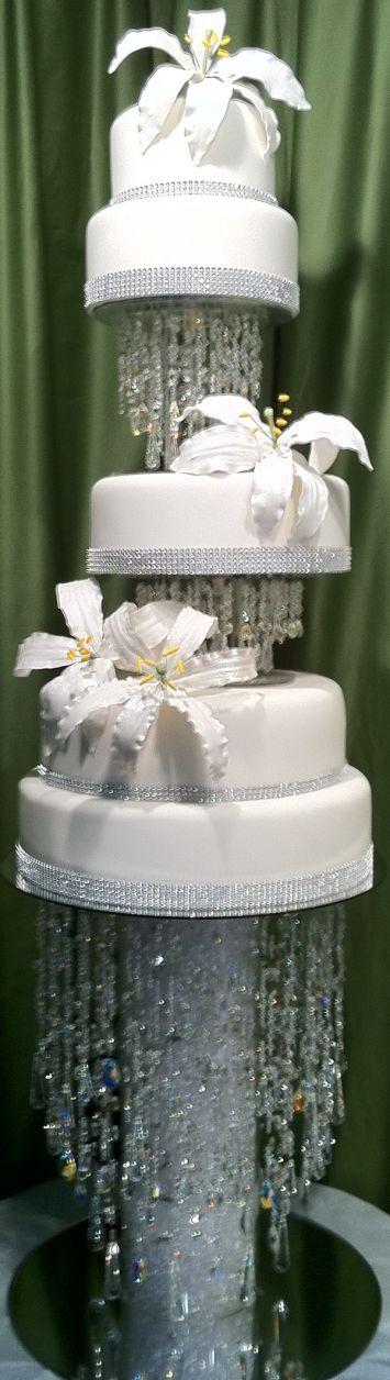 Torta de niveles de color blanco con cadenas de cristal y decoración con cinta de imitación de diamantes. #DecoracionBodas