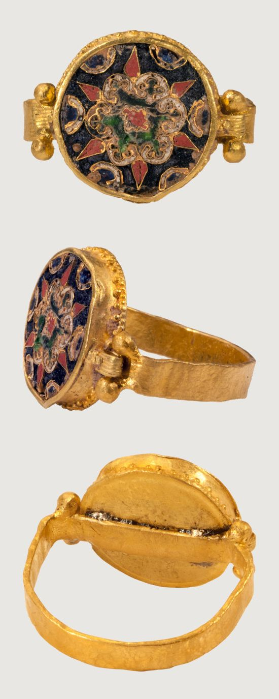 BYZANTINE CLOISONNÉ RING. Constantinople?, 10th century, gold, enamel, bezel 13 x 14 mm. This ring has been reassembled in modern times by joining a reeded gold band with four gold granules to a circular flat roundel with floral design in red, blue, green and white cloisonné enamel. The cloisonné medallion is soldered at the junction of the bezel and the hoop, which has been flattened where it passes behind the bezel. Besides some pitting on the enamel surface.