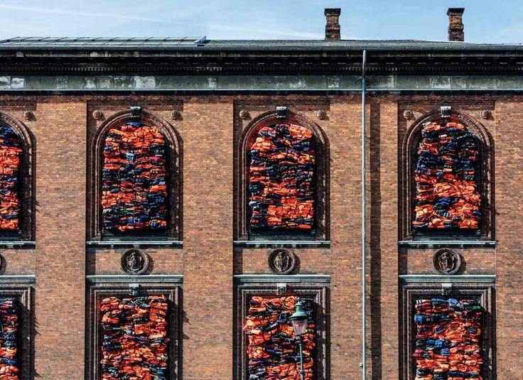 Ai Weiwei mura le finestre di un museo di Copenhagen con 3500 giubbotti di salvataggio appartenuti ai rifugiati L'artista ed attivista cinese Ai Weiwei continua a creare scenografiche installazioni monumentali, sul tema delle migrazioni umane, nelle città occidentali. Questa estate è la volta della Kunsthal Ch #arte #scultura #installazione #aiweiwei