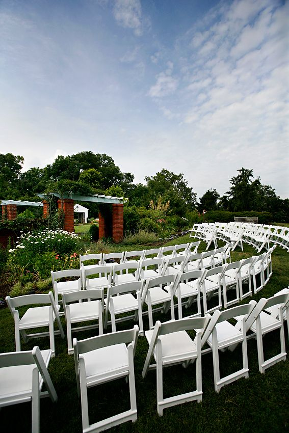 White Chairs Are Set Up By The Arbor In Garden Of River Farm Alexandria Va Preparation For Outdoor Wedding Ceremony