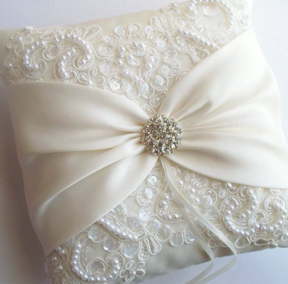 The MIRANDA is an ivory matte satin ringbearer pillow decorated with pearled and sequined alencon lace and an ivory satin sash cinched by a crystal centering. Very elegant. Shown in 8 x 8 size but 7 x 7 is also available for very young ringbearers. ***Please note: the proper way to measure a pillow is from side seam to side seam, so once a pillow is stuffed it will appear a bit smaller than the measurement. If you would like to discuss a larger size pillow with me, just convo me…