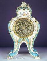 """Cette pendule faisait à l'origine partie d'une garniture qui comportait également deux pots-pourris """"à feuillage"""" et deux pots-pourris """"à bobèches"""". Cet ensemble de cinq pièces avait été livré à Madame de Pompadour (1721-1764) pour son château de Ménars. De forme rocaille, la pendule est ornée d'un fond """"petit verd"""" très apprécié de Madame de Pompadour. Le cadran a été exécuté par l'horloger parisien Jean Romilly (1714-1796) et le reste de l'objet est en porcelaine de Sèvres."""