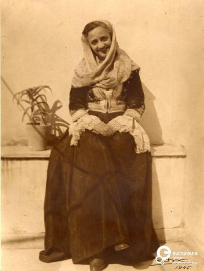 """φωτογραφία γυναίκας με φορεσιά από τα νησιά του Αργοσαρωνικού. Επιγραφή: """"1945"""".  Ημερομηνία: 1945 ,   Ημερομηνία δημιουργίας: 1945 Περίοδος: 1945 Συλλέκτης: Peloponnesian Folklore Foundation   Ίδρυμα: Europeana Fashion  www.europeanafashion.eu"""