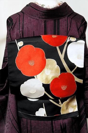 黒の地に凛と浮かび上がる白梅紅梅が美しく目をひく開き名古屋帯です。
