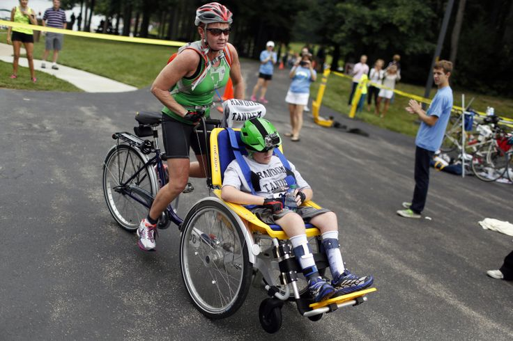 Laurie Booher takes off with her son Collin during the Columbus Challenge Triathlon on Saturday, Aug. 09, 2014 in Columbus, Indiana. Collin ...