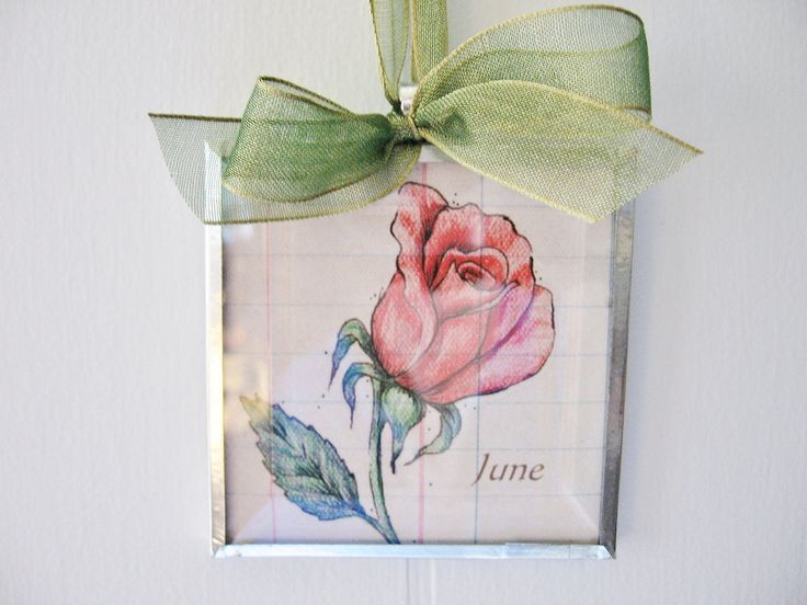 """Birth Month Flower June Rose 3x3 Beveled Glass Art Print Ornament. June Rose Pearl Good Health Celebrate a special occasion such as a birthday, anniversary, first date, baby's birth or any other memory with a hanging art bevel. On the back of each month it explains that months flower birthstone and attribute. These art bevels look lovely hanging on a peg, door knob or on a wall. I have sandwiched a 3"""" x 3"""" print of my original art between a beveled glass and a flat glass panel. It has…"""